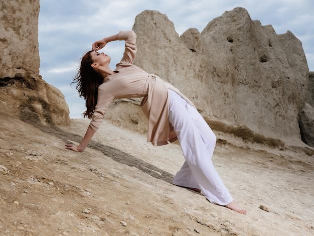 Kobieta siedząca na piasku w eleganckim stylu