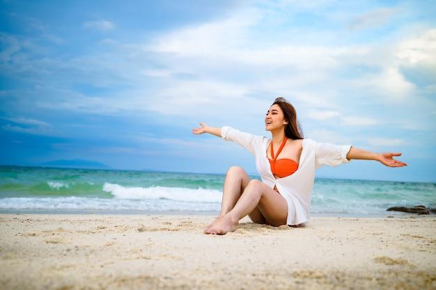 Kobieta siedząca na plaży na wyspie koh munnork, rayong, tajlandia
