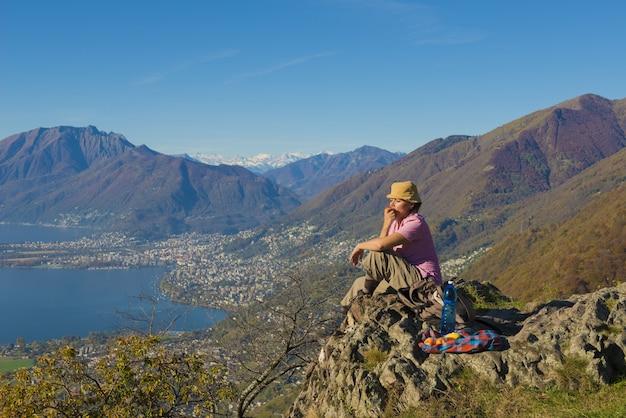 Kobieta siedząca na skale z pięknym widokiem na góry w pobliżu brzegu morza