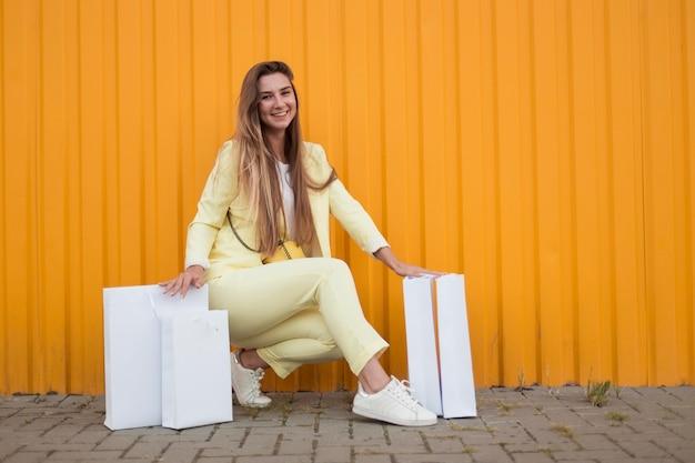 Kobieta siedząca obok białych toreb na zakupy