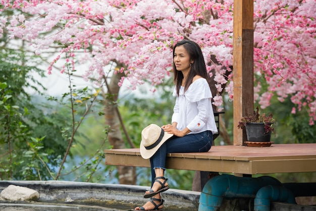Kobieta siedząca pod wiśniowym drzewem