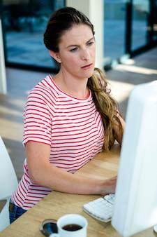 Kobieta siedząca przy biurku, wpatrująca się uważnie w swój komputer
