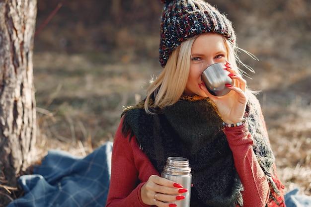 Kobieta siedząca przy drzewie w wiosennym lesie przy termosie na drinka