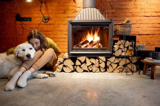 Kobieta siedząca przy kominku z białym psem w przytulnym i loftowym wnętrzu domu