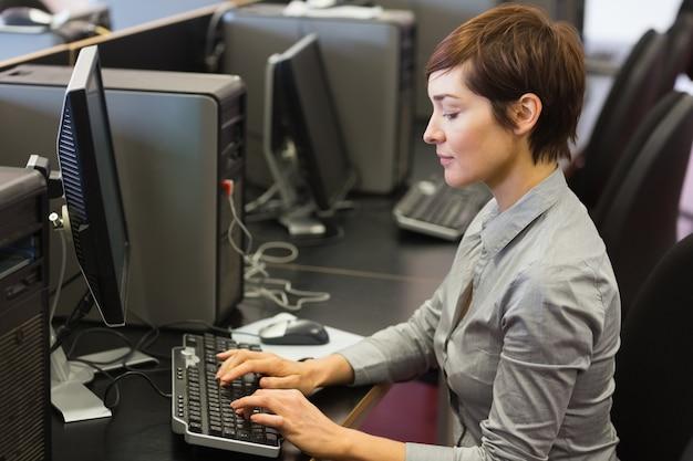 Kobieta siedząca przy komputerze w sali komputerowej