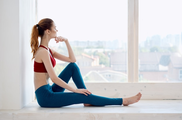 Kobieta siedząca przy oknie rekreacyjny trening sportowy
