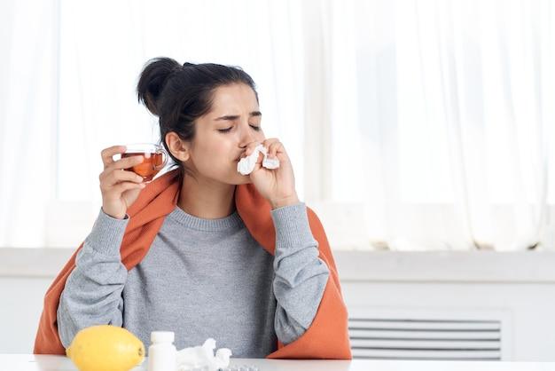 Kobieta siedząca przy stole i leczenie problemami zdrowotnymi zakażenia pigułkami