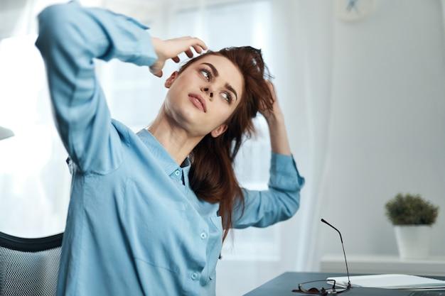 Kobieta siedząca przy stole przed lustrzaną fryzurą czesania