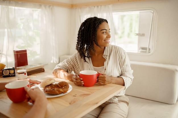 Kobieta siedząca przy stole w przyczepie kempingowej, obozująca w przyczepie. para podróżuje furgonetką, wakacje w kamperze, wakacje w kamperze