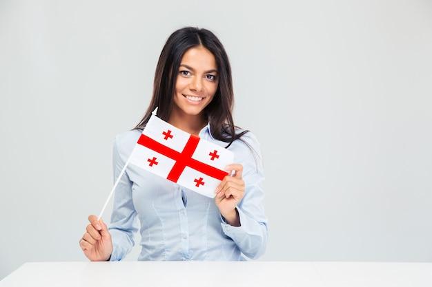 Kobieta siedząca przy stole z flagą gruzińską