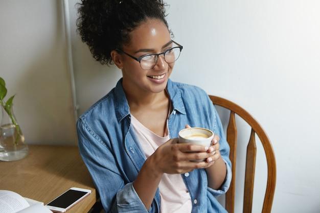 Kobieta siedząca przy stole z kawą