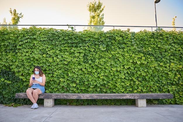 Kobieta siedząca samotnie na ławce z maską wirusa.