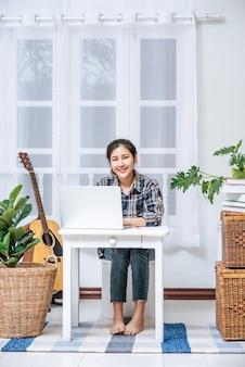 Kobieta siedząca szczęśliwie z laptopem przy stole.