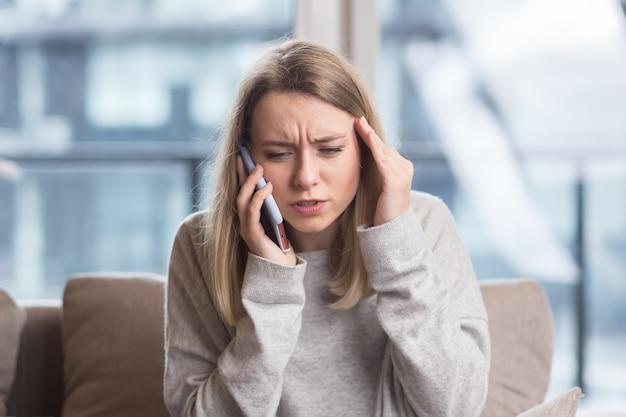 Kobieta siedząca w domu na kanapie z silnym bólem głowy próbująca zadzwonić do lekarza przez telefon