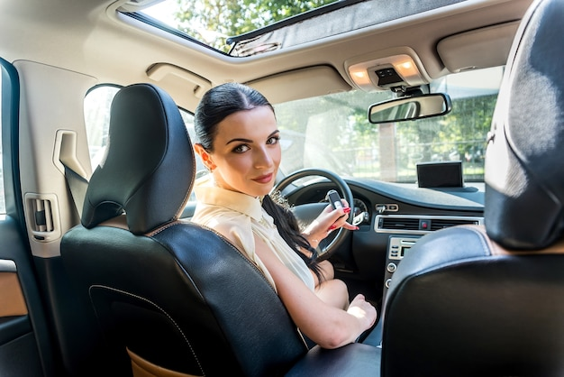 Kobieta siedząca w nowym samochodzie oferująca klucz