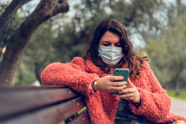 Kobieta siedząca w parku chroni się za pomocą maski medycznej podczas pisania na swoim smartfonie.