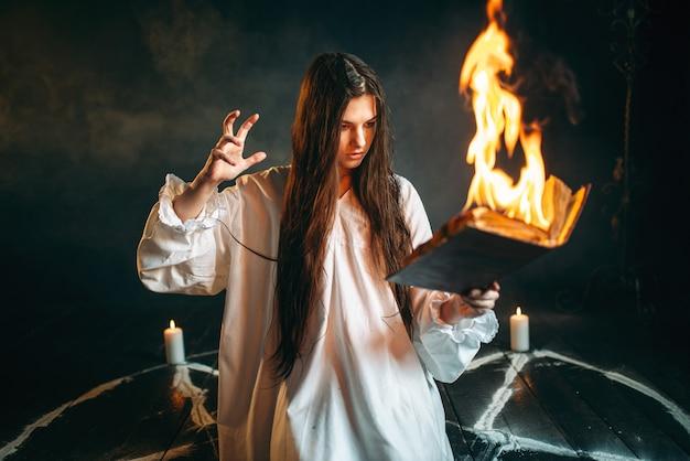 Kobieta siedząca w płonącym kręgu pentagramu, magia