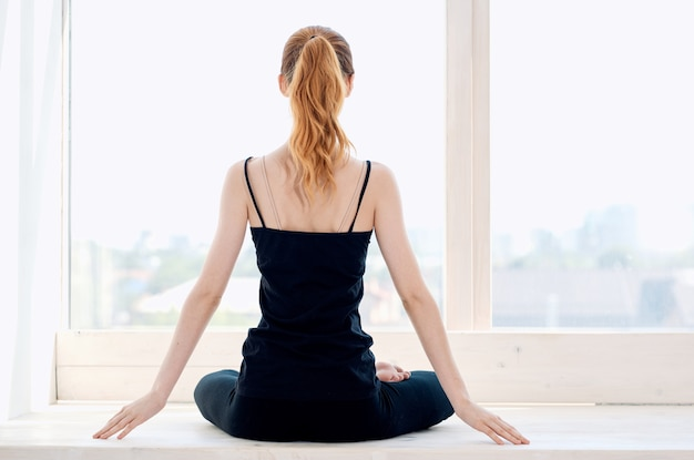 Kobieta siedząca w pozycji lotosu, ćwiczenia jogi medytacji w pobliżu okna