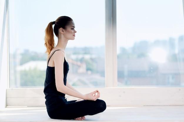 Kobieta siedząca w pozycji lotosu medytacja odpoczywa w pobliżu okna
