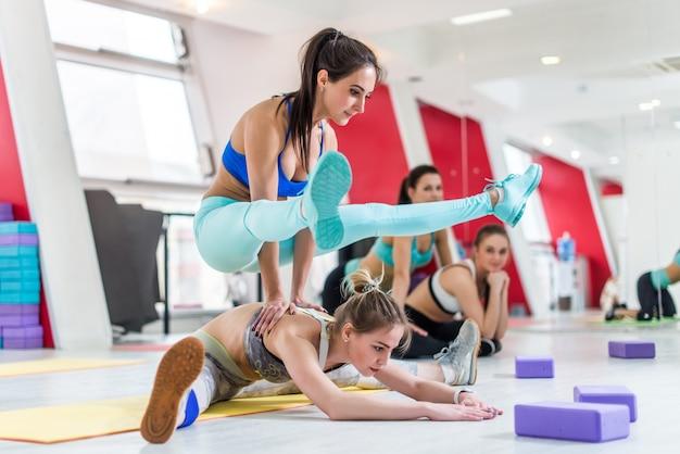 Kobieta siedząca w pozycji siedzącej z szerokim kątem do przodu i inna sportsmenka robi joga świetlikowa stojąca na plecach swojego partnera