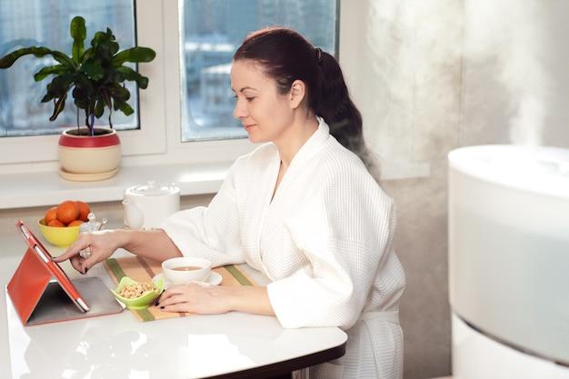 Kobieta siedząca z komputerem typu tablet na tle nawilżacza