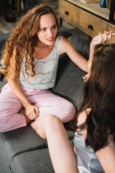 Kobieta siedząca z przyjacielem wzruszając ramionami