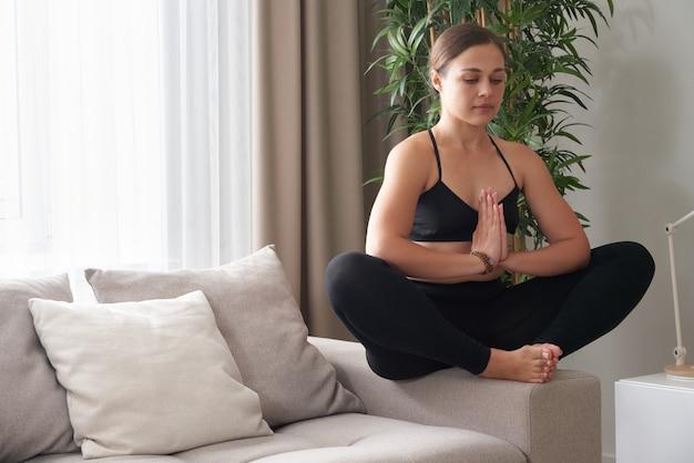Kobieta siedząca ze skrzyżowanymi nogami na kanapie w pozycji lotosu medytująca w domu w salonie