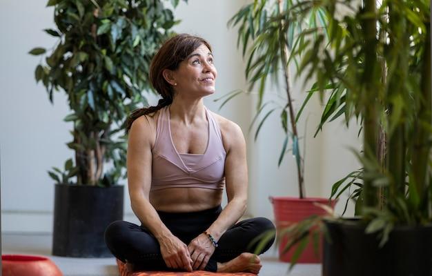 Kobieta siedząca zrelaksowana w sali do jogi, wyglądająca przez okno