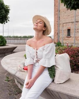 Kobieta siedzi i cieszy się słońcem