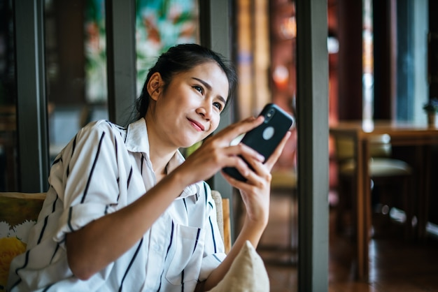 Kobieta siedzi i gra jej inteligentny telefon w kawiarni