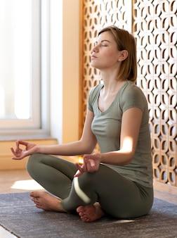Kobieta siedzi i medytuje pełne ujęcie