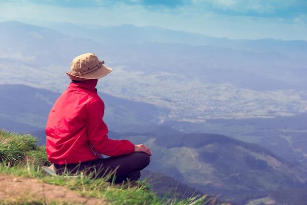 Kobieta siedzi i patrzy z daleka na góry