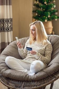 Kobieta siedzi i płaci za zakupy online kartą kredytową za pomocą laptopa i smartfona.