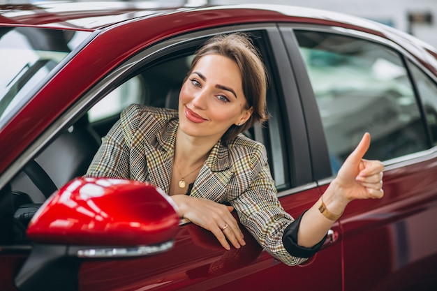 Kobieta siedzi i samochód w samochodzie showrrom