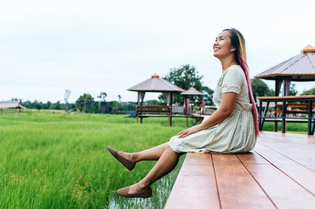 Kobieta siedzi i zrelaksować się na moście z drewna z nogami zwisającymi
