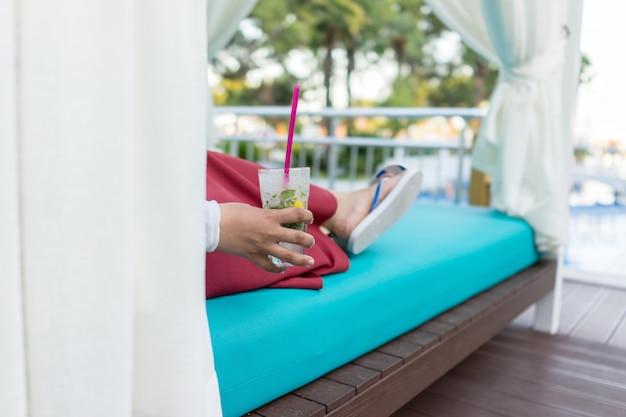 Kobieta siedzi na basen ośrodka i picie soku