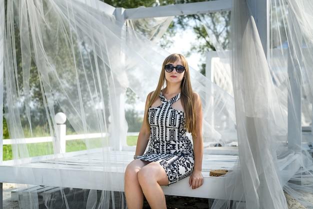 Kobieta siedzi na białej huśtawce w parku i cieszy się letnim dniem
