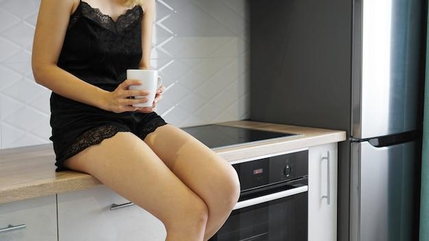 Kobieta siedzi na blacie w białej nowoczesnej kuchni