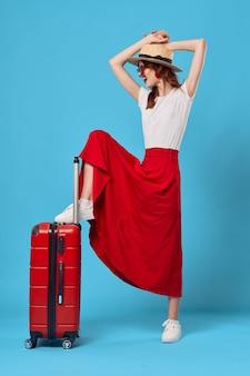 Kobieta siedzi na czerwonej walizce podróż styl życia lot niebieskim tle