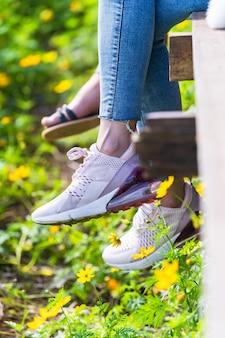 Kobieta siedzi na drewniany most i wiszące nogi w kwiat ogród