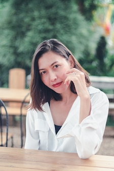 Kobieta siedzi na drewnianym krześle w restauracji