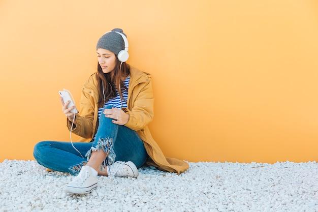 Kobieta siedzi na dywanie za pomocą smartphone słuchania muzyki na słuchawkach