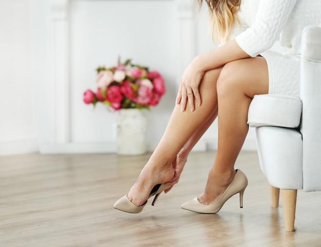 Kobieta siedzi na fotelu i nosi beżowe obcasy