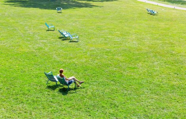 Kobieta siedzi na fotelu na środku łąki.