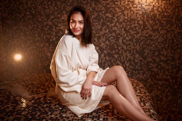 Kobieta siedzi na gorącym kamieniu w łaźni tureckiej, saunie