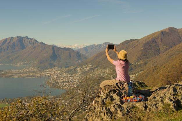 Kobieta siedzi na górze i robienia zdjęć z pięknym widokiem na jezioro w szwajcarii