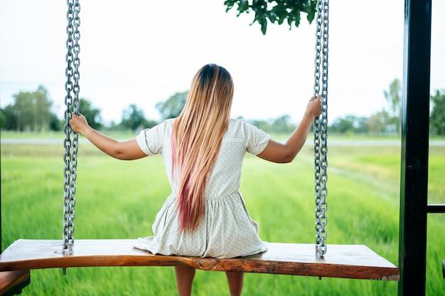 Kobieta siedzi na huśtawce i trzyma rękę na łańcuchu