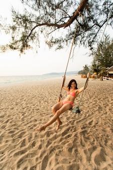 Kobieta siedzi na huśtawce na tropikalnej plaży, rajskiej wyspie.