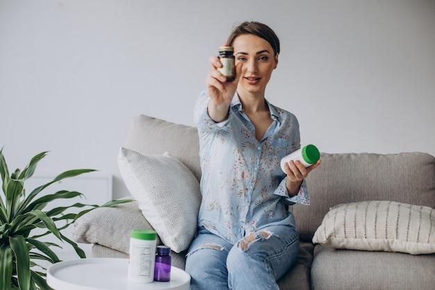 Kobieta siedzi na kanapie i trzyma tabletki z witaminami