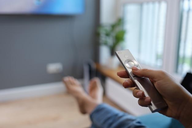 Kobieta siedzi na kanapie i trzyma w dłoniach pilota do telewizora